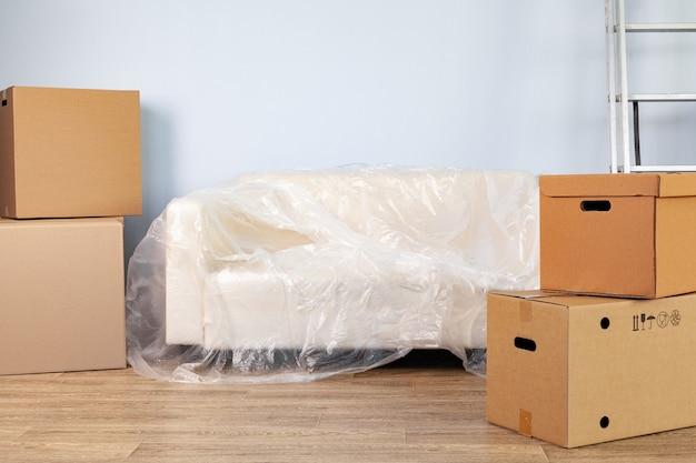 Упакованные хозтовары в коробки и упакованный диван для переезда.