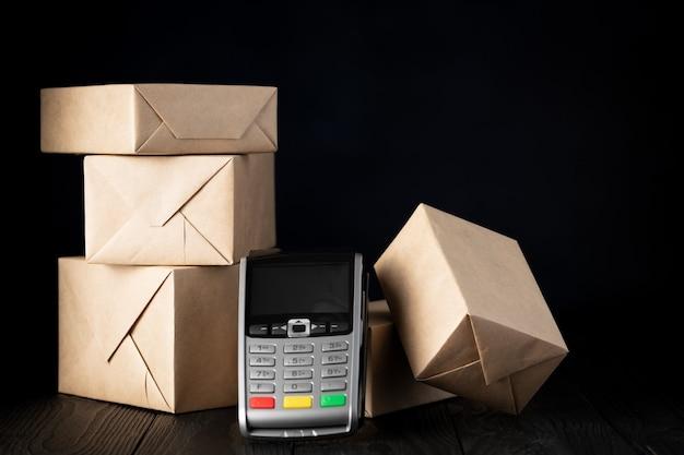 Упакованные посылки и платежный терминал на черном фоне