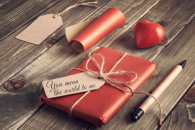 Packed present, wrapping  paper, paper, cardboard tags and and stone heart on wood, text