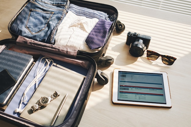 Packed suitcase on desk, tablet with eticket on screen, camera, and sunglasses