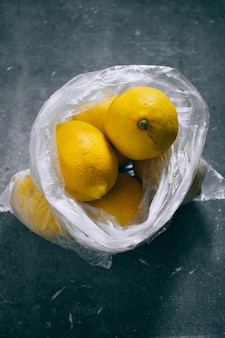 A packet of citrus, lemons on a gray background