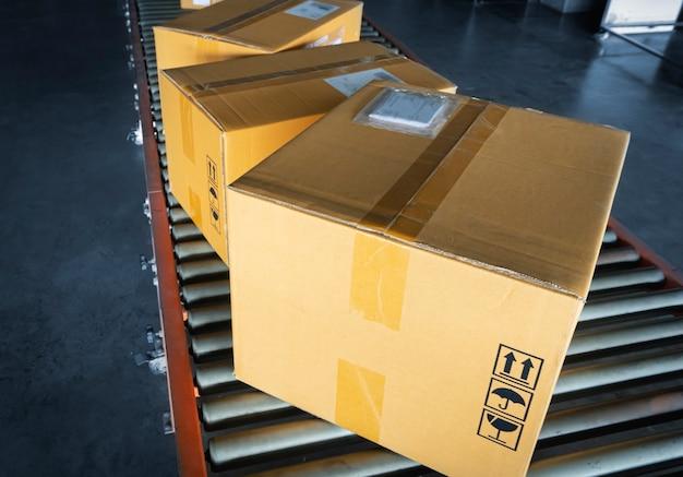 Сортировка упаковочных ящиков на роликах конвейерной ленты на складе