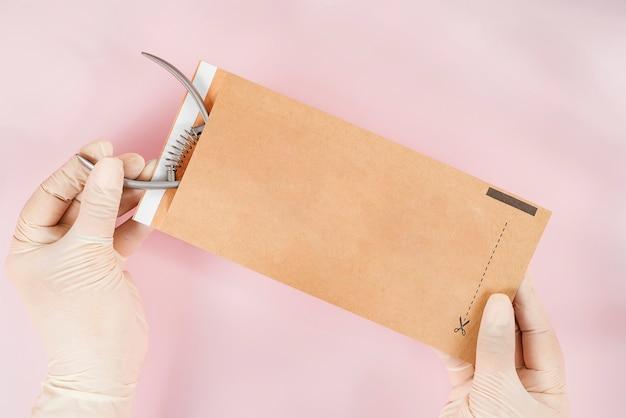 Упаковка маникюрного инструмента в крафт-пакеты перед стерилизацией в сухой духовке. инструмент для маникюра в руках мастера, изолированные на розовом фоне. закройте вверх.