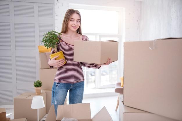 積極的に梱包。居間の真ん中に立って、カートンボックスと植物を運んでカメラに微笑んでいる美しい若い女性
