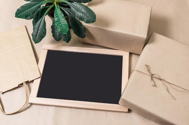 Упаковочные коробки и хозяйственная сумка на сером фоне с зеленым растением и черной доской для покупок, вид сверху.