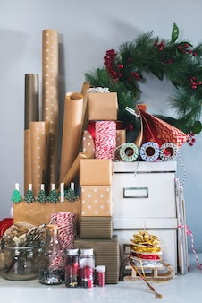 Packing boxes, gifts in kraft beige vintage wrapping paper. wreath holly berry on gray wall background. concept of preparation to new year and christmas holidays