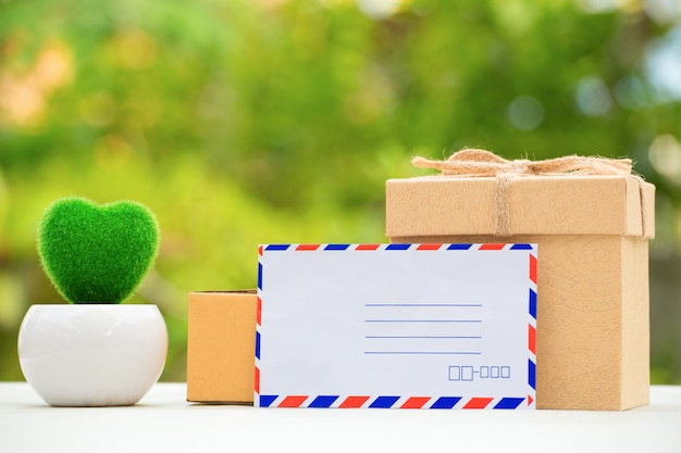 Packing brown parcels box on beautiful natural green background.