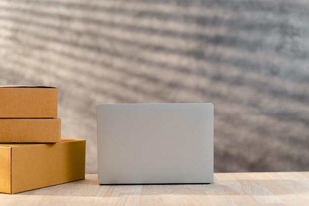 스타트업 중소기업의 홈 오피스에서 판지 소포 상자와 컴퓨터 노트북 포장