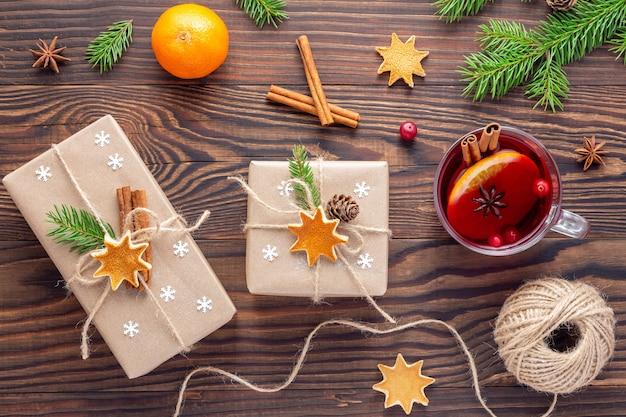 Упаковка подарков в канун рождества с чашкой глинтвейна или красного чая на коричневом деревянном столе