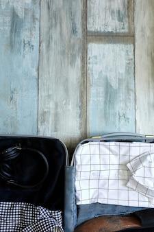 Упаковка чемодана дома с повседневными мужскими вещами, вещами - джинсами, рубашками, наушниками в чемодан для путешествий, путешествий, отпуска. скопируйте пространство.