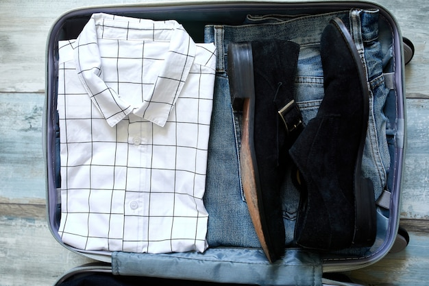 Packing suitcase at home with business man items, stuff - pants, shirts, shoes in suitcase for travel, journey, vacation