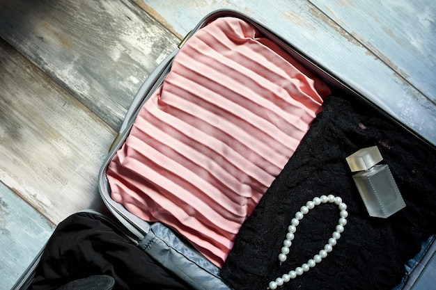 Packing suitcase at home with woman items, accessories in suitcase for travel, journey, vacation . copy space.