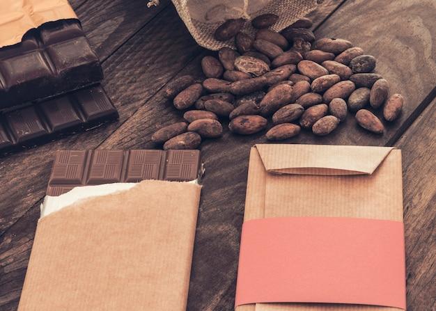 Imballaggio e spacchettamento della barretta di cioccolato con fave di cacao sulla tavola di legno