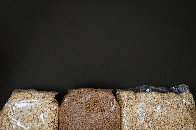 Packs of buckwheat oatmeal and pearl porridge on a black background