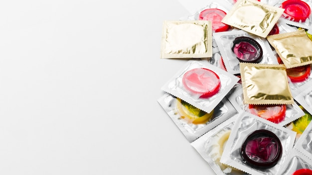 Packs of condoms on white background with copy space