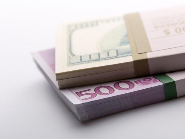 Packs of dollars and euros closeup