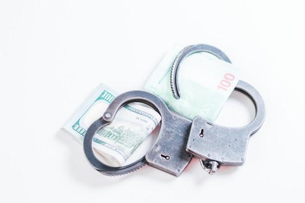 Пачки евро и стодолларовых купюр заключены в браслеты-наручники. понятие о воровстве, мошенничестве и незаконном бизнесе. коррупция. смешанная техника
