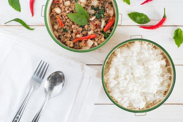 Название тайской еды pad ka prao, изображение вида сверху риса с жареной свининой с листьями базилика вилкой и ложкой на белом деревянном столе