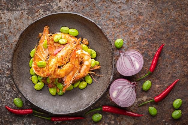 Pad ped sator goong、タイ料理、エビとエビの赤カレー炒めさびたテクスチャの背景にワビサビスタイルのプレートに貼り付け、上面図、苦い豆、ツイストクラスター豆、臭い豆