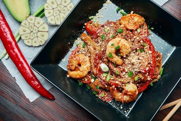 Pad тайский или phad thai - классическое тайское блюдо из вока с жареной рисовой лапшой с креветками и овощами в черной тарелке на деревянном столе. закрыть