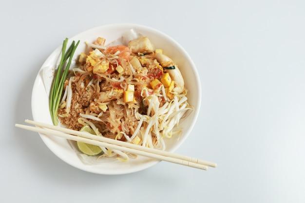 Изолированный стиль зажаренной лапши тайский с креветками и морепродуктами таиланд вызывает pad тайский, стиль stir-зажаренной лапши тайский на белизне.