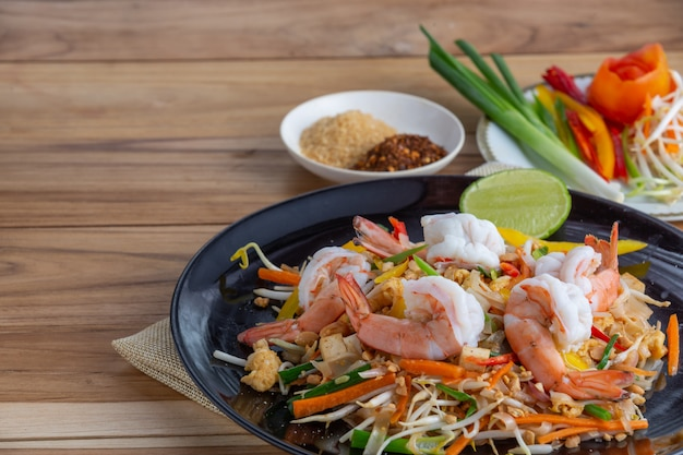 Pad thai, fresh shrimp in a black dish, placed on a wooden table.