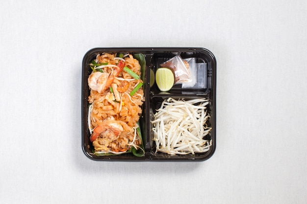 Pad thai goong sod with bean sprouts put in black plastic box, put on a white tablecloth, food box, thai food.