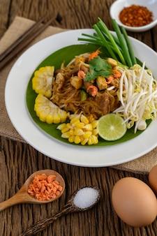 レモン、卵、木製のテーブルの調味料で白い皿にタイをパッドします。