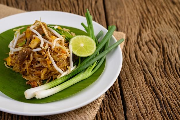 Pad тайский в белой тарелке с лимоном на деревянном столе
