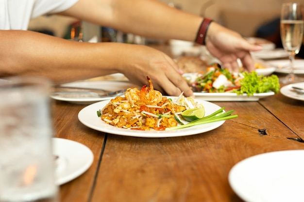 Pad thai noodles with shrimp on whit plate on wooden table in restaurant.