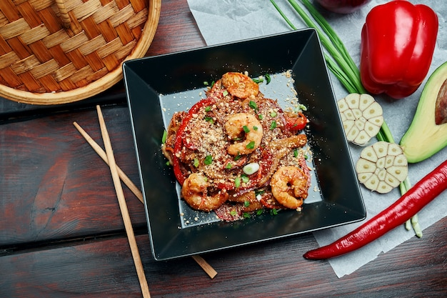Pad thai or phad thai - a classic thai dish wok fried rice noodles with shrimps and vegetables in a black plate on a wooden table. close up