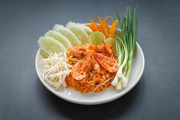 Pad thai, pud thai stir fried noodle with shrimp served with mung bean sprout, cucumber, lime, chilli and spring onion