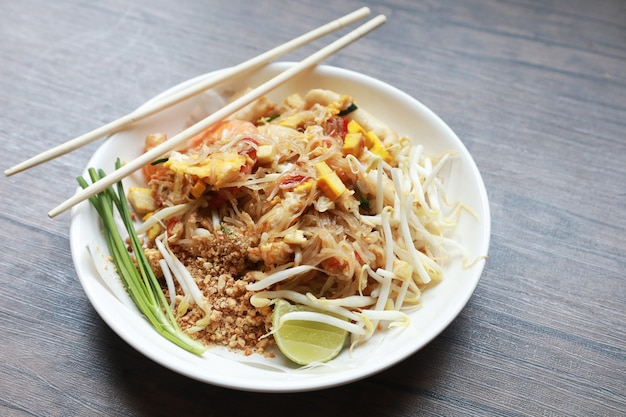 Pad thai stir fried noodle thai style with pork tofu and vegetable on plate put on wood table , the favorite food in thailand