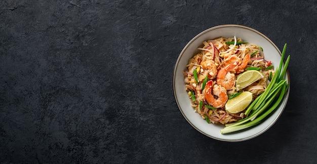 Пад тай, тайская жареная лапша с креветками и овощами на темном фоне, вид сверху, копией пространства