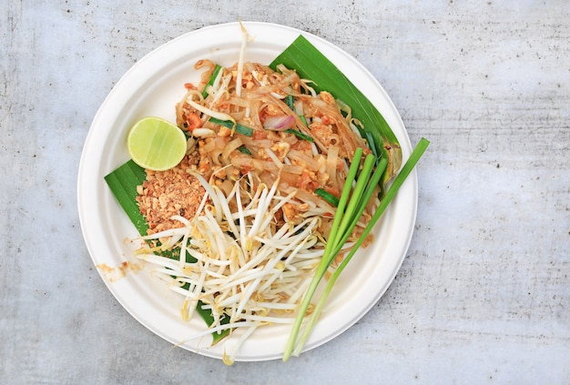 Pad thai in white foam plate on stone table with copy space. thailand's national dishes.