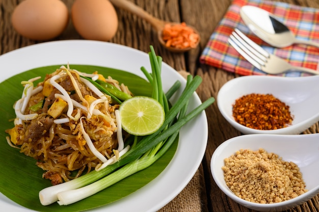 Pad thai in a white plate with lemon, eggs and seasoning on a wooden table.