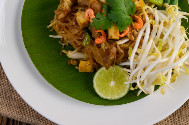 Pad thai in a white plate with lemon on a wooden table