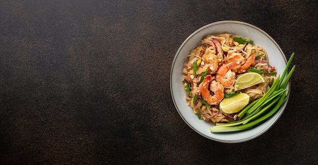 Pad thai with shrimp in a ceramic bowl on a dark background, top view, copy space. traditional thai food