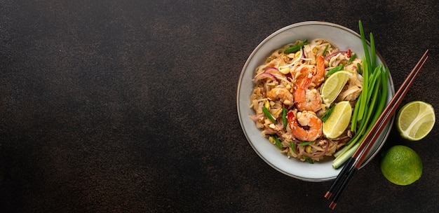 Pad thai with shrimp in a ceramic bowl on a dark background top view copy space