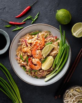 Pad thai with shrimp on a dark stone surface, top view