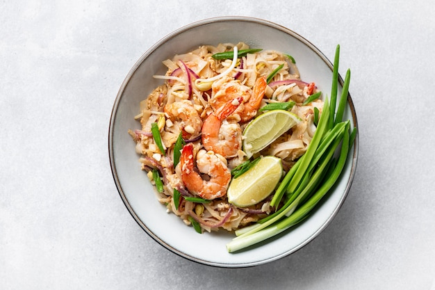 Pad thai with shrimp, sprouts and green onions on a concrete background, top view