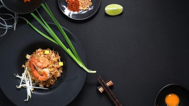Вид сверху pad thai, муха тайской лапши с креветками и яйцом в черной керамической тарелке на черном столе