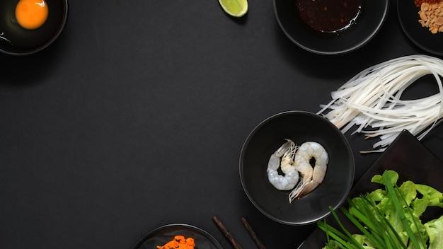 Вид сверху ингредиентов pad thai, муха тайской лапши с креветками, яйцо, в черной керамической миске