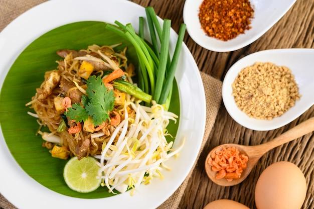 Pad тайский в белой тарелке с лимоном, яйца и приправы на деревянном столе.