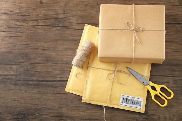 Мягкие конверты и подарочная коробка посылки на деревянном столе