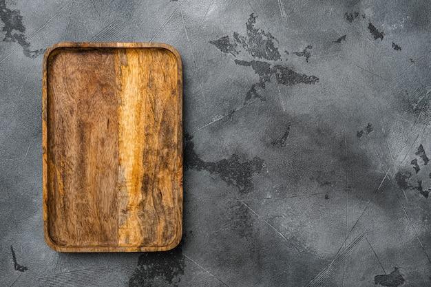 Набор лопаток для резки или сервировочной доски, плоская планировка, вид сверху, с местом для текста или вашего продукта, на фоне серого каменного стола