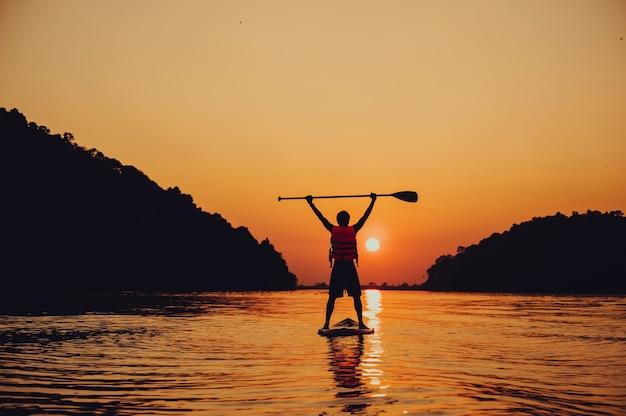 Весло стоя, силуэт человека на пляже на закате
