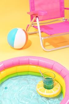 Детский бассейн с надувной подушкой в форме лимона с коктейлем, за ним шар и розовое кресло.