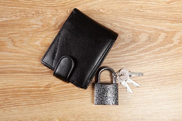 Замок и черный бумажник на деревянном столе. концепция безопасности денег