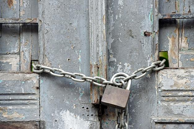 자물쇠와 닫힌 된 오래 된 문에 체인